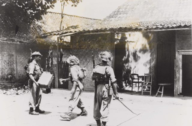 Three British-Indian soldiers burn down houses in Bekasi (West-Java, 1945). Collection NIMH.